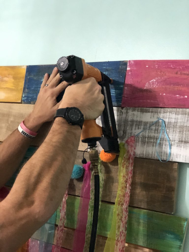 Nailing Painted Wood for Pallet Wall Colorful Backdrop for Photo or Video by Tamara Bennett of Southern ADOORnments