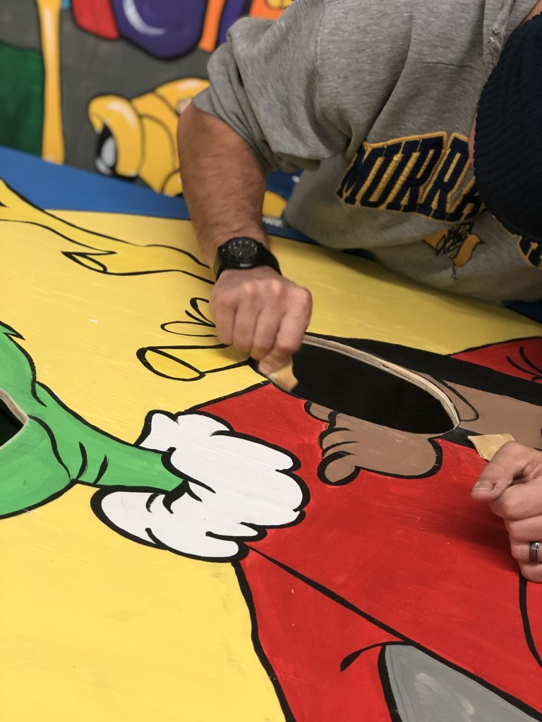 Sanding Photo Prop hole for Murray State Basketball Grinch Christmas Painted Backdrop by Southern ADOORnments