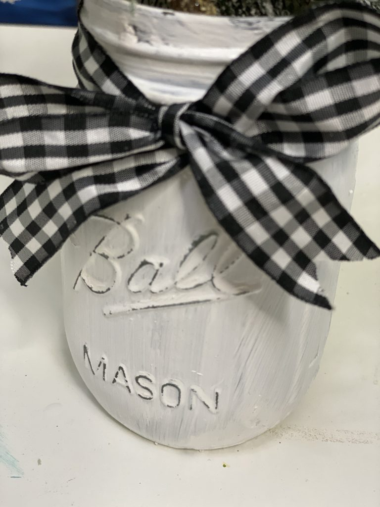 Closeup of Painted Christmas Mason Jar with Buffalo Plaid Ribbon by Southern ADOORnments