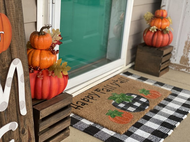 Fall front porch with stacked pumpkins on wood crate with buffalo plaid layered rug by southern a-door-nments