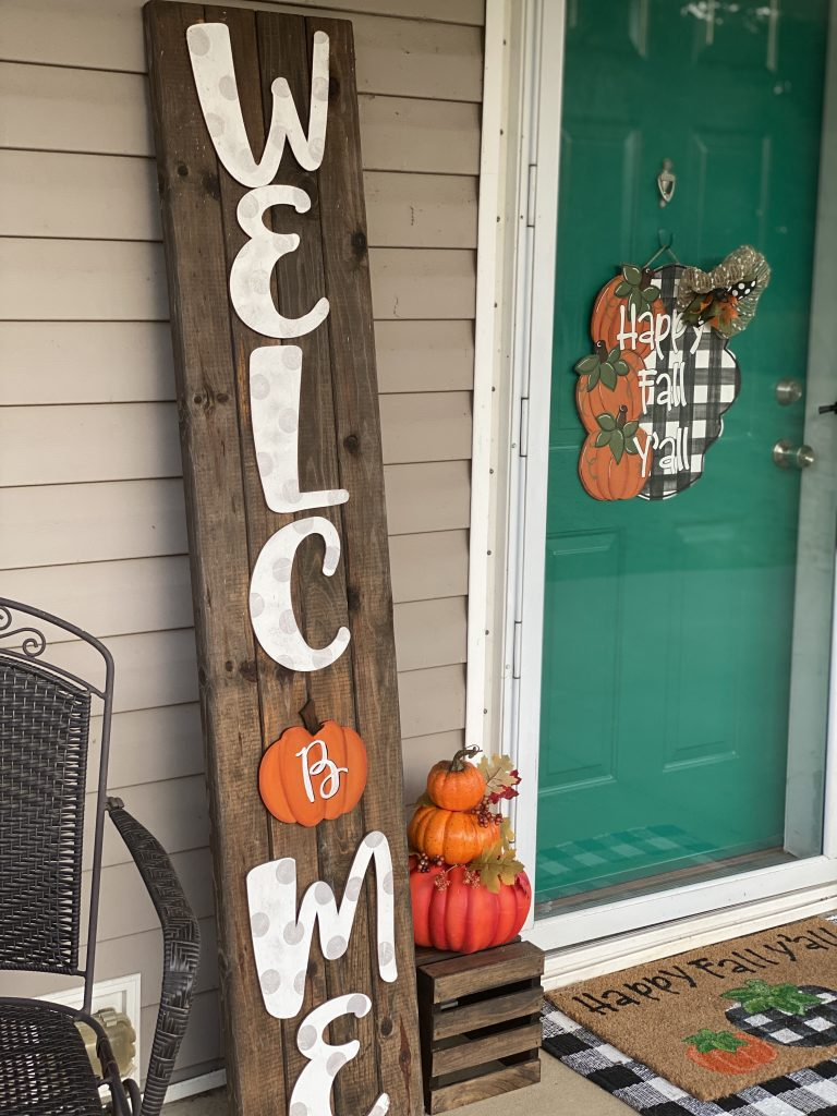 Welcome sign with monogram pumpkin accent on buffalo plaid front porch by southern a-door-nments