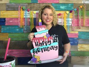 Tamara Bennett holding the Happy Birthday Door Hanger by Southern A-Door-nments