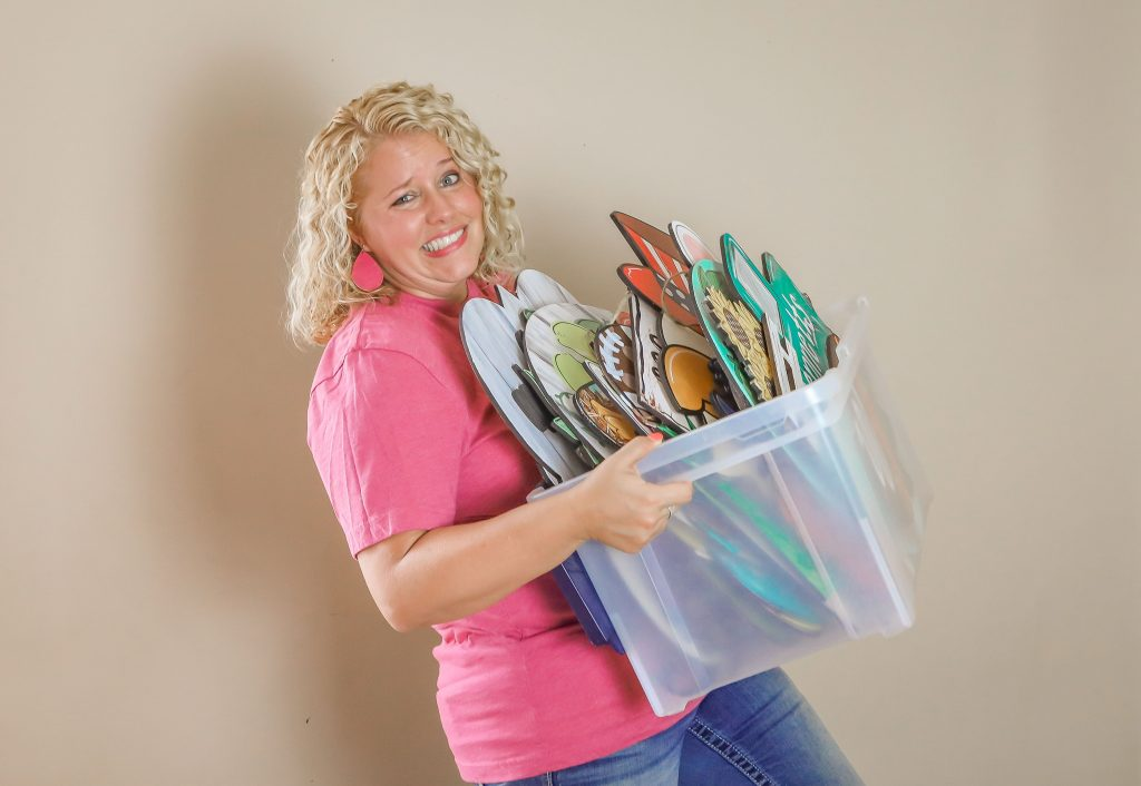 Tamara holding a tote of painted door hangers