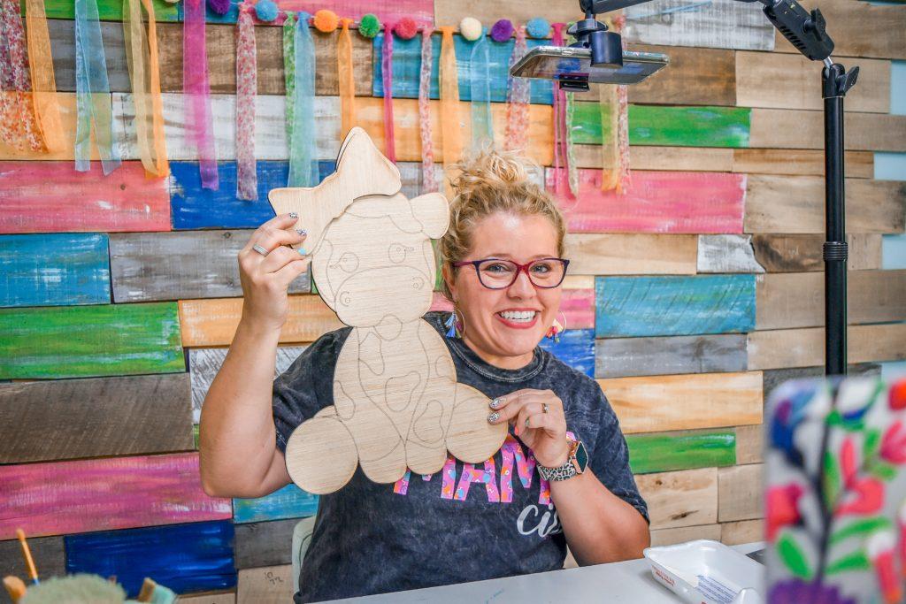 Tamara holding a blank wood baby cow door hanger