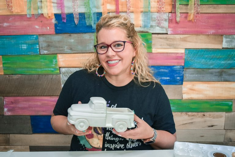 Tamara Bennett holding a white unpainted ceramic truck