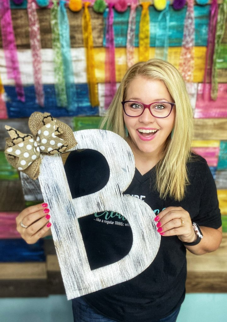 Tamara holding a painted letter B door hanger with a burlap bow
