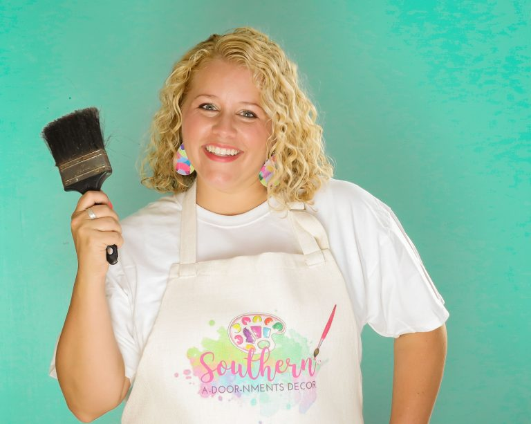 Tamara holding a paint brush and wearing a painting apron