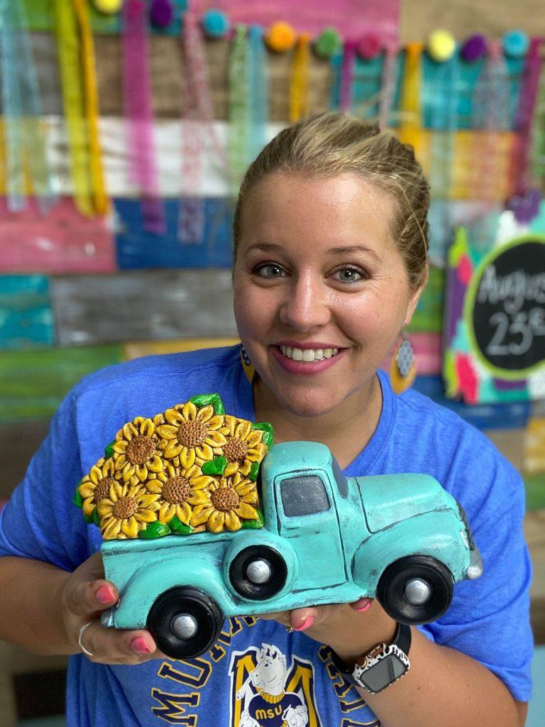 Tamara holding ceramic truck with sunflowers