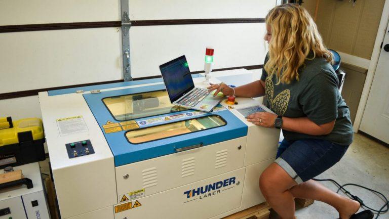 Tamara using a computer to send a design to the Thunder Laser Machine.