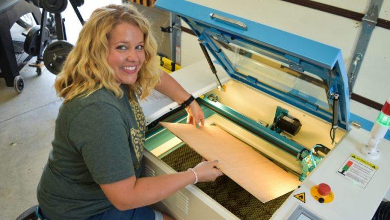 Tamara putting wood in the Thunder Laser machine.